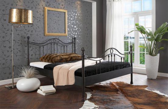 Metallbett 204.00 Ancona von Dico Möbel in Kombination mit goldenen Akzenten & grauer Wand