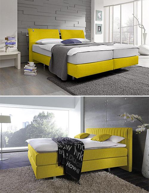 Gelbes Boxspringbett vor grauer Wand